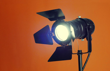A studio spotlight facing the camera on a colorful background