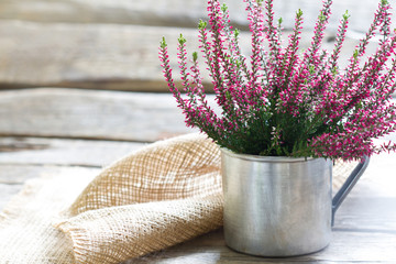 Autumn heather in cup on wooden boards background