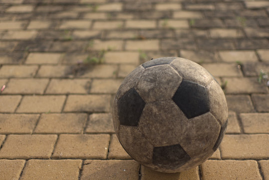 soccer ball placed on the brick floor And the light from the sunset shining down