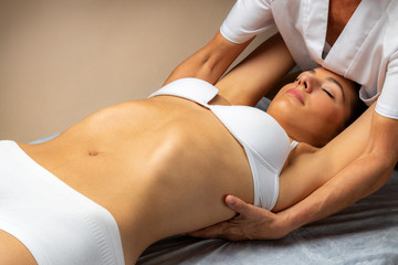 Osteopath manipulating shoulder blades of young female patient.