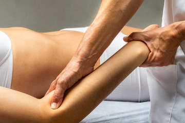 Physiotherapist applying pressure on female forearm muscle.