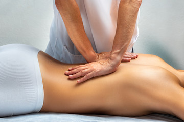 Physiotherapist applying pressure with hands on female bac