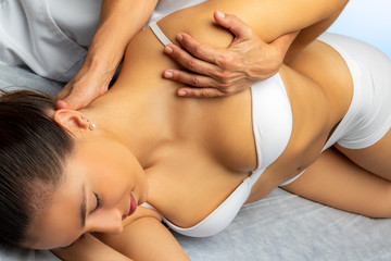 Physiotherapist doing shoulder and neck treatment on woman.
