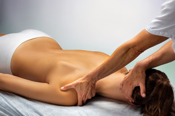 Physiotherapist manipulating neck and shoulder on female patient.