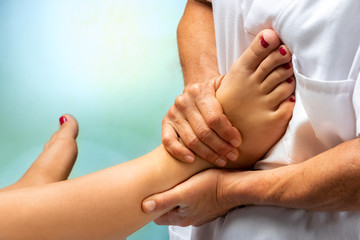 Physiotherapist massaging human foot