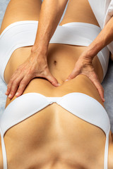 Top view of physiotherapist applying pressure on woman's stomach.