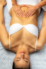 Top view of therapist doing treatment on female tummy.