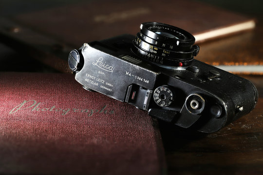 GERMANY - MAY 25, 2019: Heavy used Leica M4 camera with photo album on wooden table. The Leica M4 is a 35 mm rangefinder camera produced by Ernst Leitz GmbH from 1966 - 1975.
