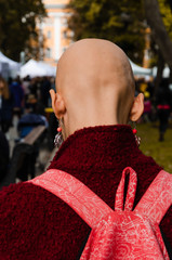 Young bald woman with long earrings. Dressed in a burgundy coat with a pink backpack. Back view. Outdoors