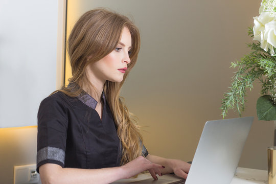 Portrait of young beautiful female receptionist in uniform using laptop at work