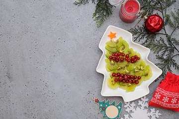Creative edible vegan christmas tree, food art. Food for kids and festive table. Tree made from kiwi on a white tree plate