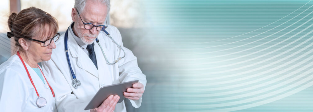 Two doctors discussing about medical report on tablet; panoramic banner