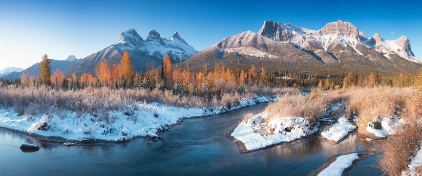 Panorama of autumn sunrise at The Three Sisters mountain with colorful trees Canmore, Alberta with reflection in calm water of Policeman creek surrounded by trees and bushes. First snow in mountains