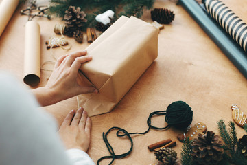 Hands wrapping christmas gift in craft paper and pine branches, cones, gingerbread cookies, thread, cinnamon on rural wooden table. Wrapping stylish christmas gifts concept