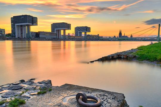 Ankerplatz am Rhein bei den Poller Wiesen in Köln während Sonnenuntergang. Blick auf die Kranhäuser und den Kölner Dom.