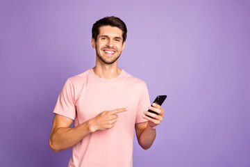 Portrait of his he nice attractive cheerful cheery glad content guy wearing pink tshirt holding in hands recommending digital device isolated on violet purple lilac pastel color background