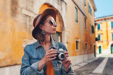 Attractive tourist with a retro camera Wall mural