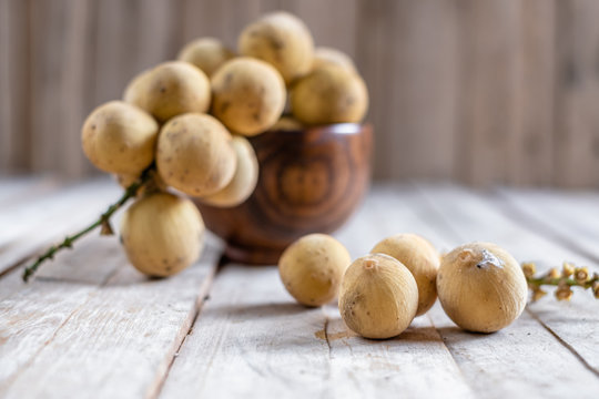 Clusters of exotic Thai fruit called Longkong or lansium parasiticumor southern langsat on wooden table and background. It is a famous sweet tropical fruit in southeast asia.