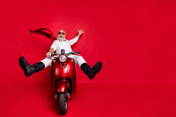 Full size photo of funky grandfather screaming raising his palm riding scooter wearing white sweater trousers pants boots isolated over red background