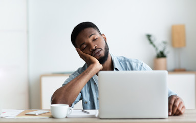 Exhausted African American worker felt asleep at workplace