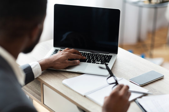 Black businessman working on laptop on his workplace