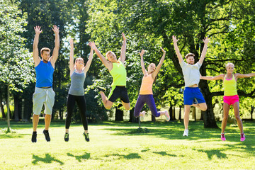fitness, sport and healthy lifestyle concept - group of happy people jumping high at park in summer