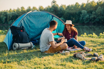 Fototapeten Camping friends on camping outdoor by the lake or river