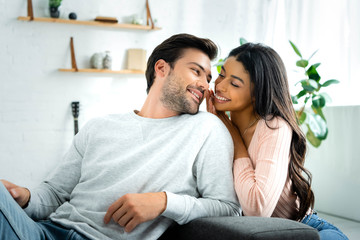 african american woman and handsome man smiling and looking at each other in apartment