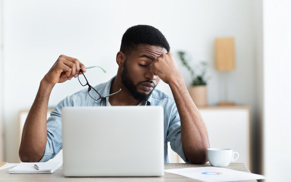 Tired african american employee having headache after working on laptop