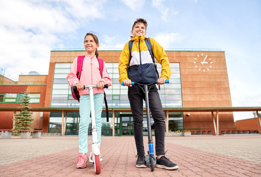 education, childhood and people concept - happy school children with backpacks and scooters outdoors