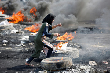 A demonstrator runs between burning tires during a curfew, two days after the nationwide anti-government protests turned violent, in Baghdad