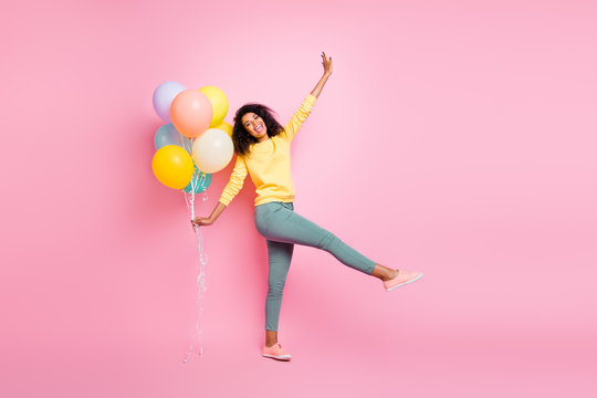 Full length photo of beautiful pretty dreamy lovely careless enjoy love like have good lucky mood holding many baloons in hand walking straight in casual jumper isolated pastel pop color background