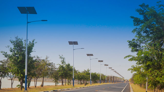 solar street light lamp post led with panel system on the road with green tree and blue sky for background energy saving concept.