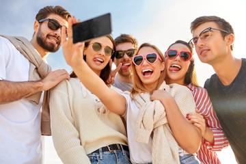 friendship, leisure and people concept - group of happy friends taking selfie by smartphone in summer