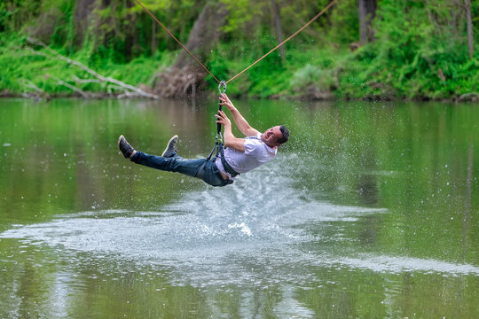 young man flying down on zipline over the river, extreme sport