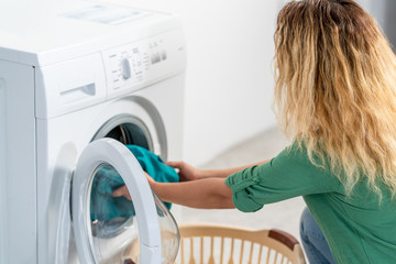 Young woman, load the wash machine for cleaning laundrys
