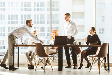 A team of young businessmen working and communicating together in an office. Corporate businessteam and manager in a meeting. desktop against the background of the pan window, free space for text