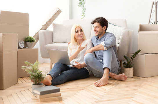 Young Couple Relaxing Sitting With Laptop On Floor Indoor