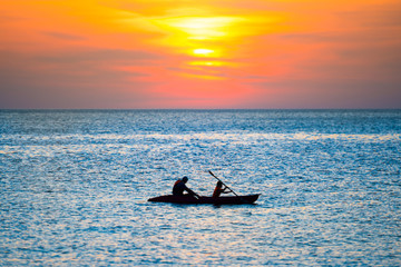 Orange sunset over blue sea and silhouette of kayak in rippled water