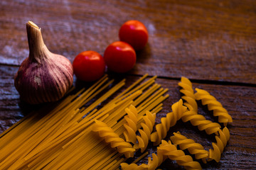 Spaghetti, cherry tomatoes and garlic on a wooden board.