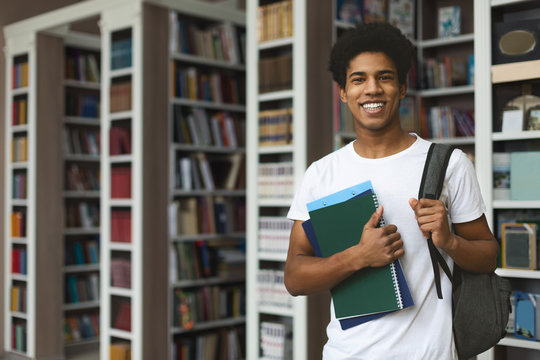 Handsome afro student posing on bookshelves background