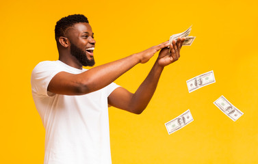 Happy african american guy throwing out money banknotes