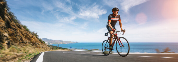 Mature Adult on a racing bike climbing the hill at mediterranean sea landscape coastal road