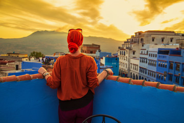 Foto op Plexiglas Marokko Girl looks at the famous blue city from above. Sunset.