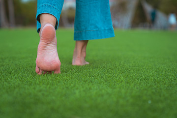 jeans barefoot walking on the grass