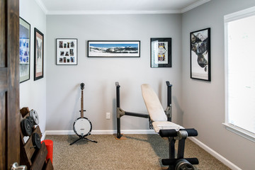 Man cave Music room inside a 1950's style home with musical instruments and a workout area