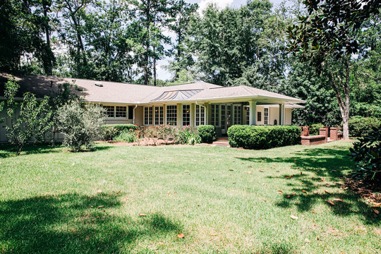Back Rearview of exterior white cream brick 1950's house with black shutters and a large porch patio and also with a lawn lot with curb appeal