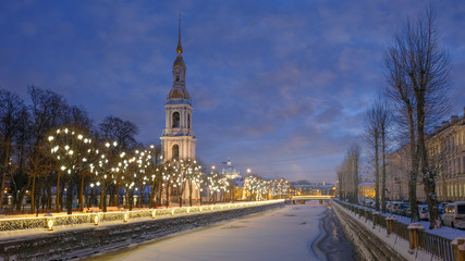 The bell tower of the Naval Cathedral of St. Nicholas on winter evenings with Christmas and New Year lights in St. Petersburg Russia