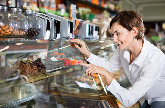 Female customer examining desserts in confectionery