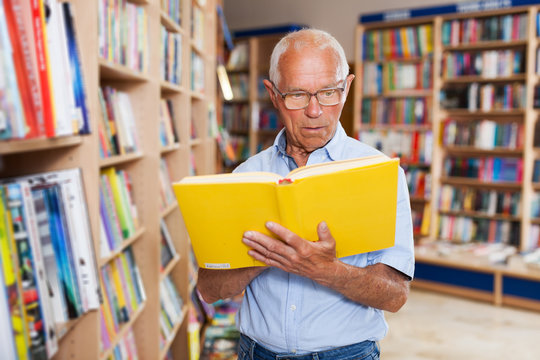 man absorbedly searching for interesting books